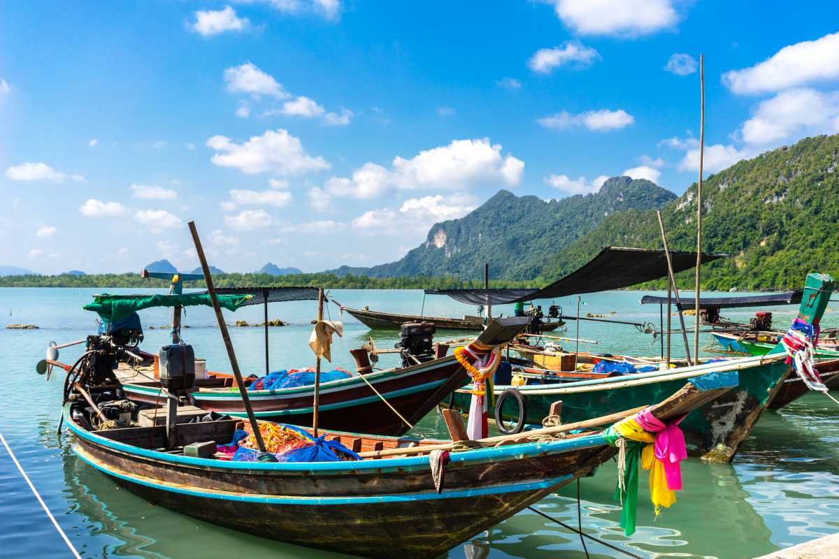 1200 Long tailed boats docked at the pier at Khnom Beach shutterstock 599659718